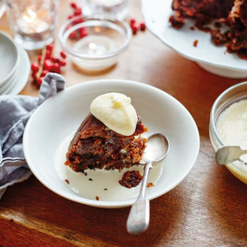 Figgy's Christmas Pudding in a white bowl with cream and a spoon